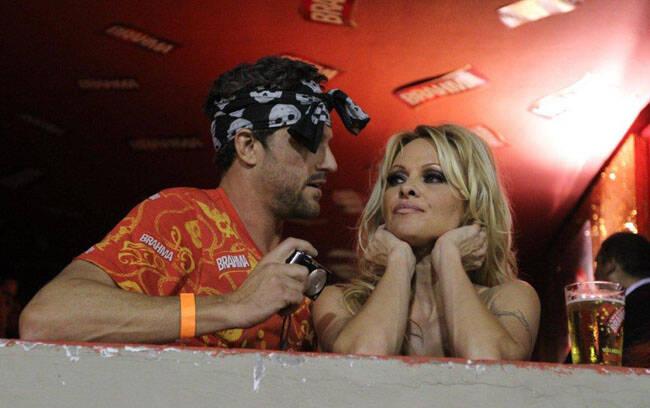 Pamela Anderson e seu namorado estavam por lá também. Pamela toda-toda, dando mil beijos no gatão
