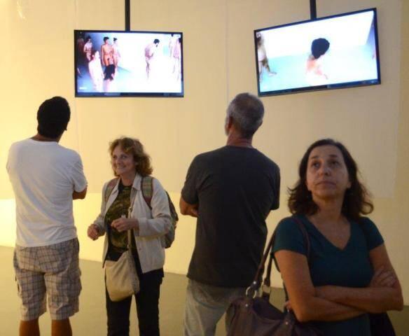 Visitantes assistindo a vídeo instalação da mostra 'Torniquete'