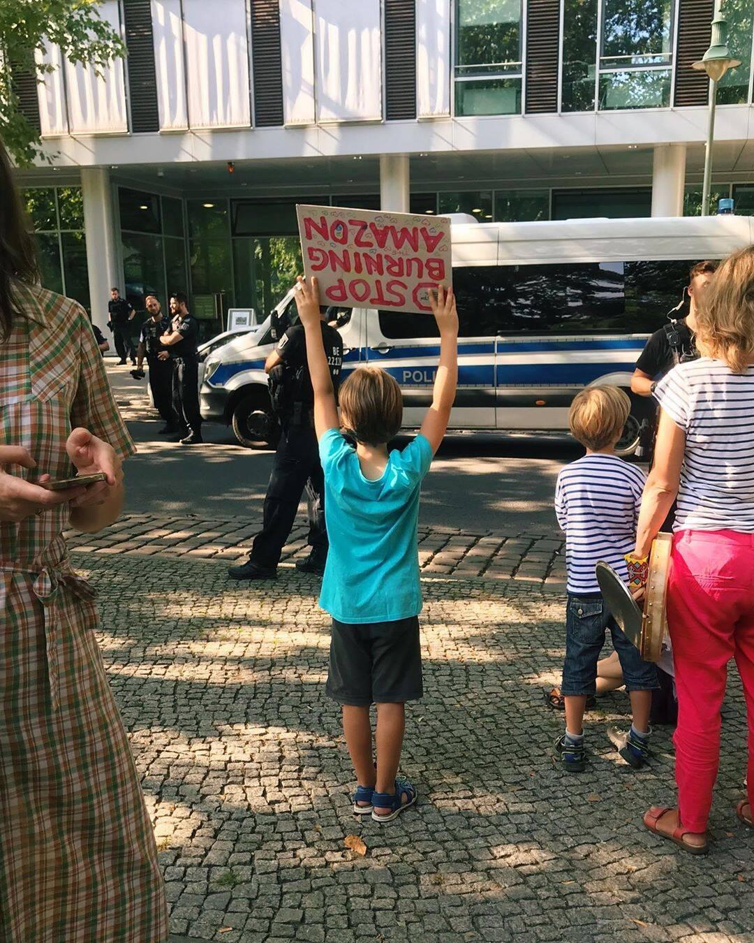 """Criança com o cartaz """"Parem de queimar a Amazînia"""", ena embaixada do Brasil em Berlim /Foto: Reprodução"""