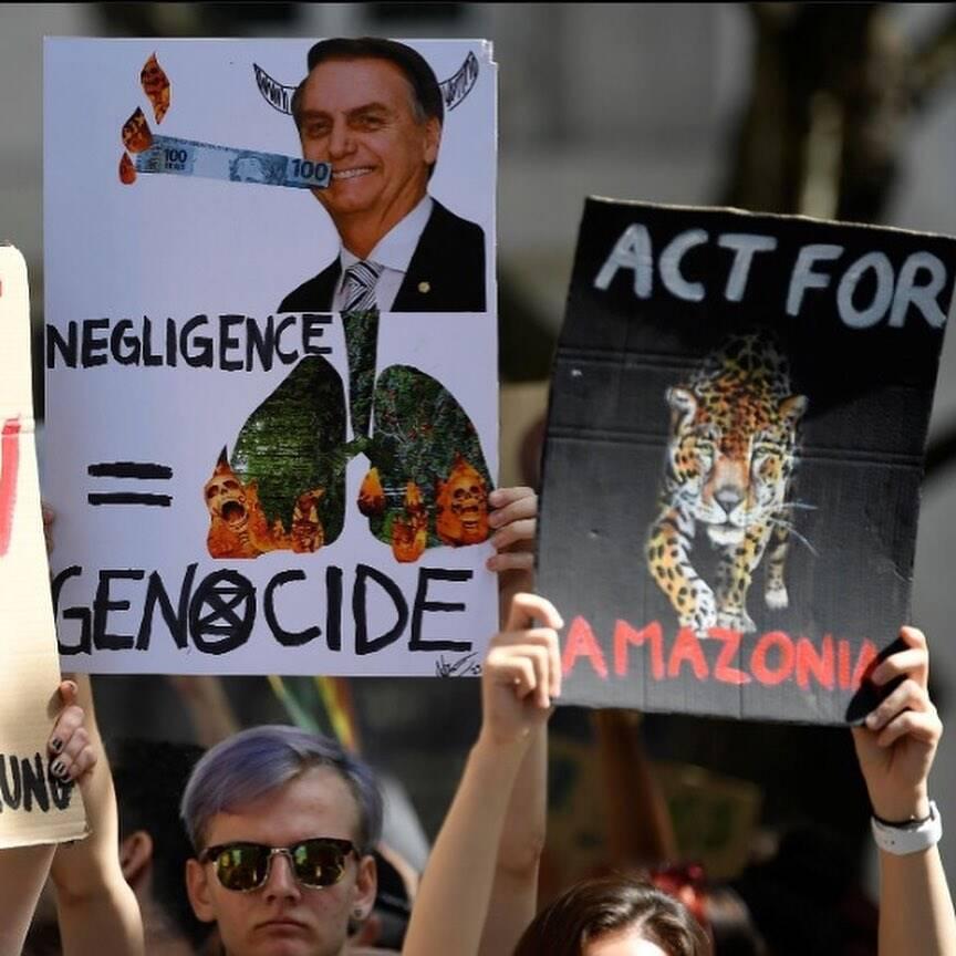 """O cartaz com a imagem de Bolsonaro: """"Negligência = Genocídio"""", em Londres /Foto: Reprodução"""