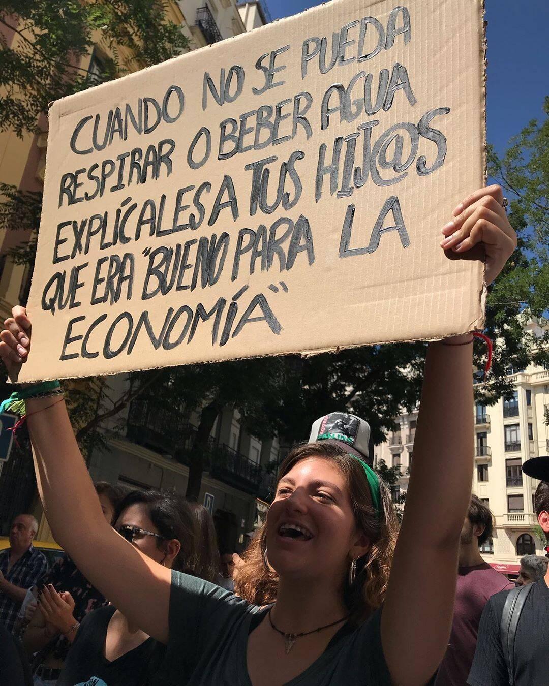 """O aviso da manifestante: """"Quando não se puder mais respirar ou beber água, explica aos seus filhos que 'era bom para a economia'"""", em Madri /Foto: Reprodução"""