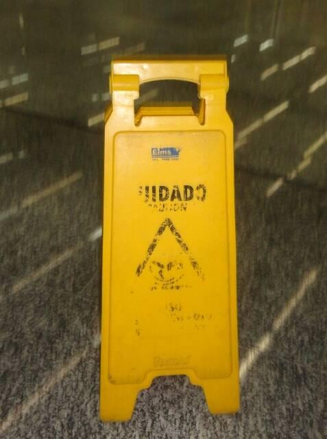 Uma das placas que indicam o piso molhado, no Galeão: as letras apagadas impedem que cariocas ou turistas leiam o aviso