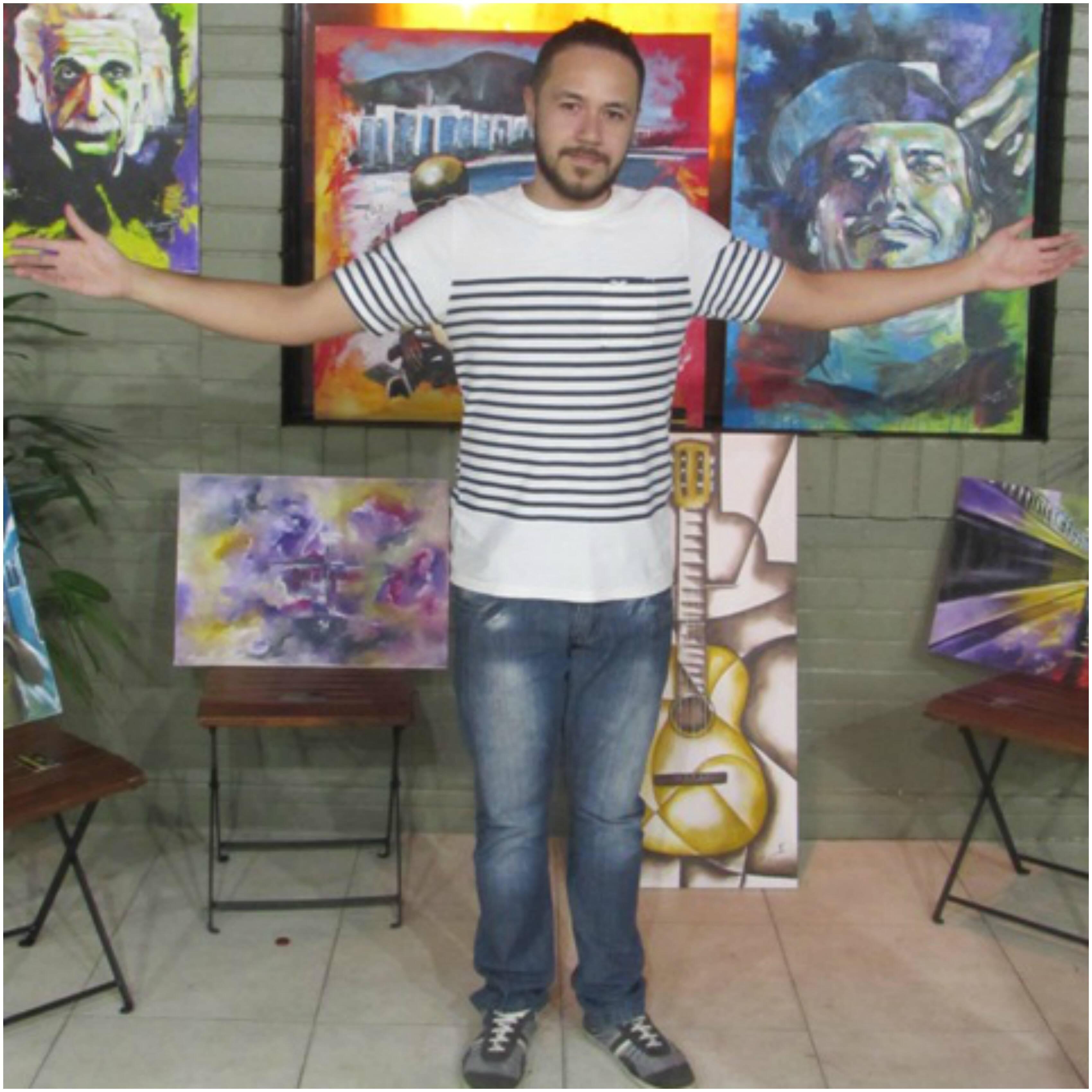 Vitor Nascimento, dono da galeria, diante das telas de sua autoria e de outros artistas locais / Foto: divulgação