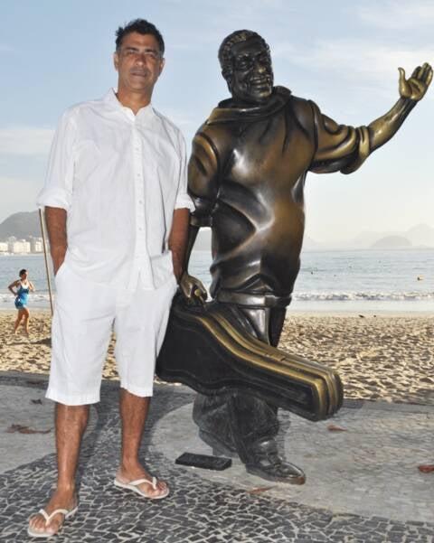 """Tony Teixeira e a estátua """"adotada"""" de Dorival Caymmi, na Praia de Copacabana  / Foto: Américo Medeiros"""
