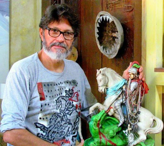 O artista plástico Raimundo Rodriguez ao lado de uma imagem de São Jorge, santo de devoção e inspiração na sua arte/ Foto: Diogo Rodrigues