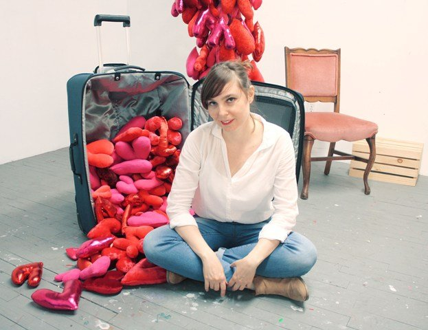 Julia, a mala e a penca de corações despencando do teto/ Foto: divulgação