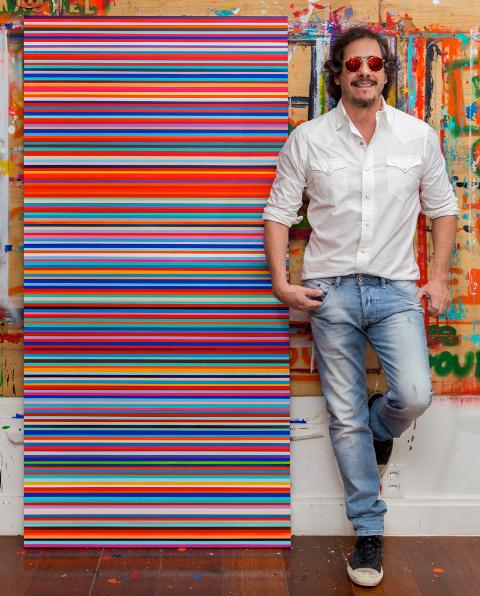 """O artista Marcelo Catalano ao lado de uma de suas """"barras de cores"""" / Foto: divulgação9"""