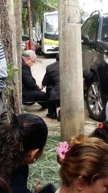 Dom Orani Tempesta, sentado no chão de uma rua em Santa Teresa, espera o tiroteio acabar digitando no celular / Foto: José Alves