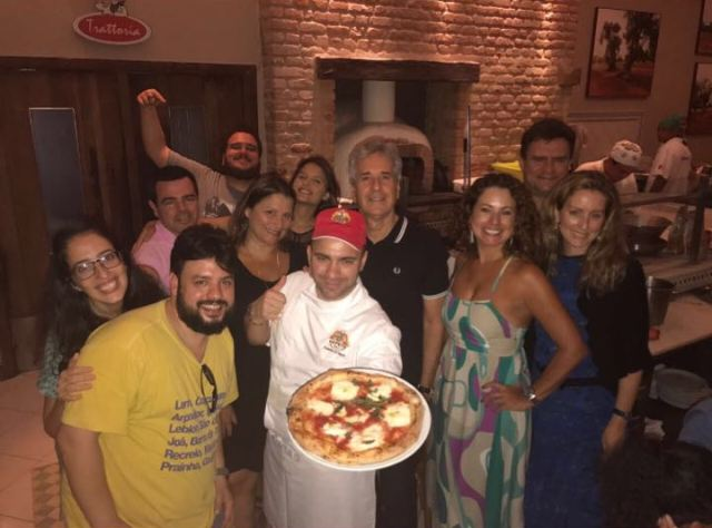 O pizzaiolo Davide Civitiello segurando a premiada Pomodorosa entre os clientes da Capricciosa, no Jardim Botânico / Foto: Divulgação